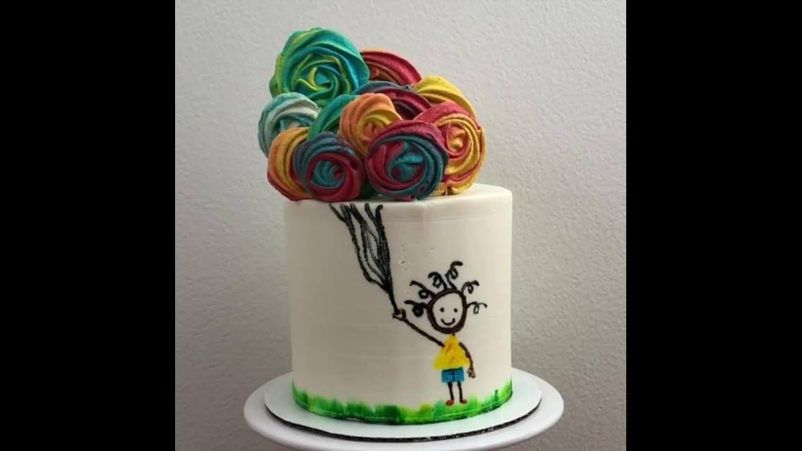 Bolo decorado com desenho e pirulitos como balões