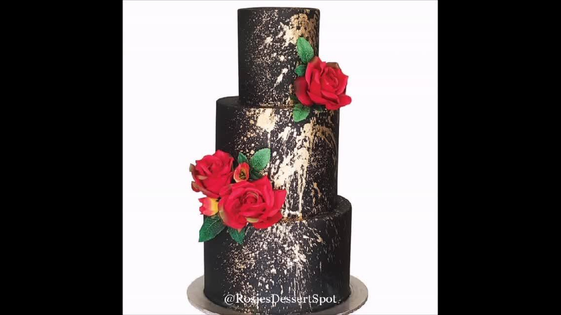 Bolo preto com detalhes dourados e rosas vermelhas