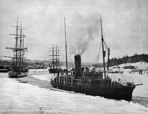 Black and white photograph of ship cutting a path for icebound vessel.
