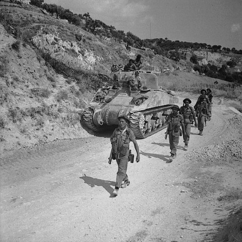 Six soldiers advancing past a tank on a narrow road. Three other soldiers are positioned on top of the tank.