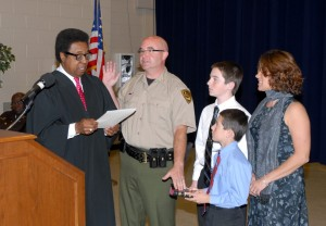 From left, District Court Judge Randolph Baskerville administers the oath of office to VGCC Chief of Police Sean Newton, as his sons, Collin and Anthony, hold the Bible and his wife, Michelle, looks on. (VGCC photo)