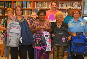 VGCC Warren Campus faculty and staff hold some of the book bags donated to J-Jireh Services; in front, from left, campus coordinator/Warren Early College liaison Faye Goode, J-Jireh director Gertie Williams Crute, Basic Skills coordinator/instructor Edna Scott and security officer Helena Jenkins; and in back, from left, administrative assistant Lisa Rodwell, Office Administration instructor Jessica Harvey, campus Dean Mitch Evans and campus custodian James Burwell. (VGCC photo)