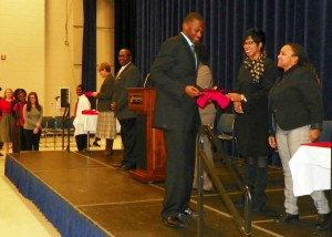 Students walk across the stage and receive recognition certificates.
