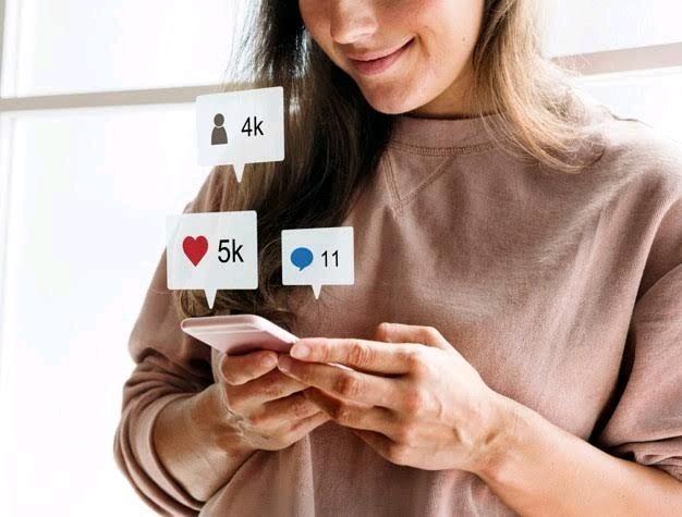 Imagem de mulher utilizando smartphone com balões saindo do aparelho representando os likes, compartilhamentos e comentários