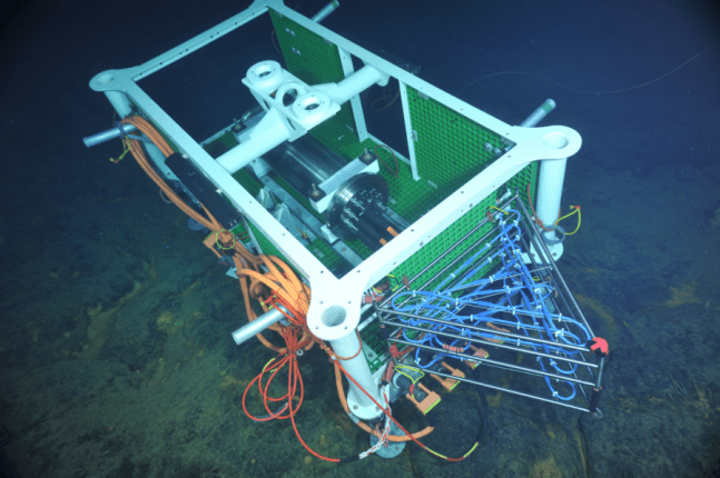 Medium-power junction box installed in the ASHES hydrothermal field of Axial Seamount's caldera. The titanium cylinder inside the node frame hosts power converters, data ports, and shore-linked communication capabilities. This J-box also hosts a cabled 3D thermistor array (the triangular-shape frame with blue cables) that was deployed for testing during the expedition. Credit: NSF-OOI/UW/CSSF