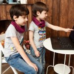 Two kids sitting in front of a laptop. The younger kids is pointing at the laptop screen.