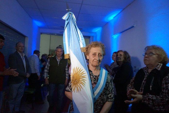 Socia de la mutual lleva la bandera Argentina en el marco de la inauguración de Esquiú Salud