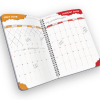 Open spiral-bound planner with months.