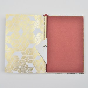 Open notebook with pocket and gold geometric design.