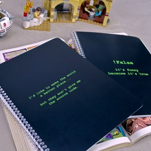 Scene of spiral-bound notebook with a coding joke cover.