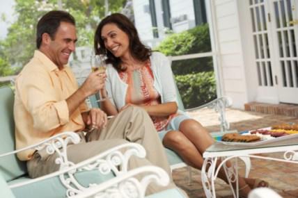 Couple Enjoying Snacks And Wine On Patio Land