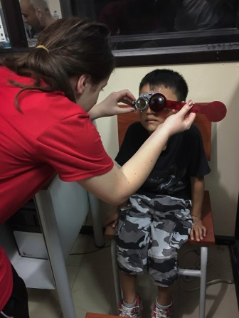 a young boy receives his eye exam from one of the Optometrist