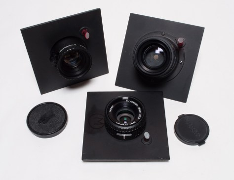 Three enlarger lenses with lens boards: Schneider Componon-S enlarger lens 2.8 55mm, El-Nikor 80mm 5.6 enlarger lens and Rodenstock enlarger lens 5.6 135mm.