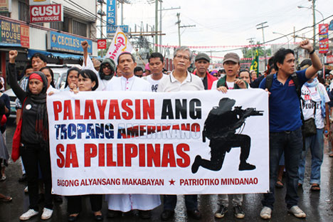 US TROOPS OUT NOW!  Participants of the People's Caravan in Zamboanga City oppose the US-PH war exercises and the continued US intervention.  Satur Ocampo (with eyeglasses), president of Bayan Muna and Makabayan Coalition, joined Mindanaons in defending national sovereignty.  (davaotoday.com photo by Kai A. Rosello)