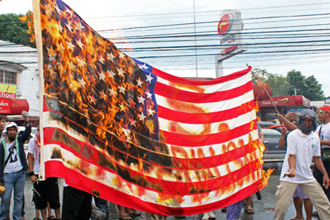 IN FIRE.  Participants of the Mindanao-wide Lakbayan against US intervention and plunder burn an American flag in Zamboanga City.  They opposed the presence of US troops in the country and asserted national sovereignty.  (davaotoday.com photo by Irika A. Rosello)