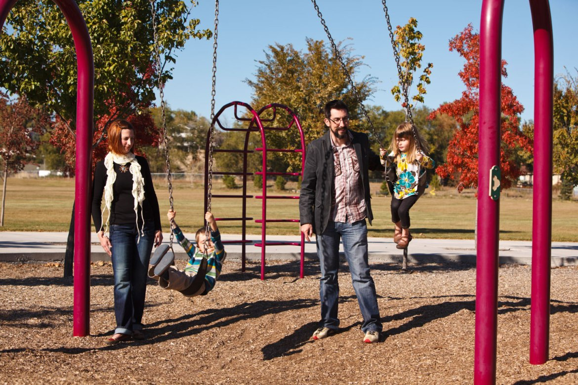 Family plays on the swings at the park