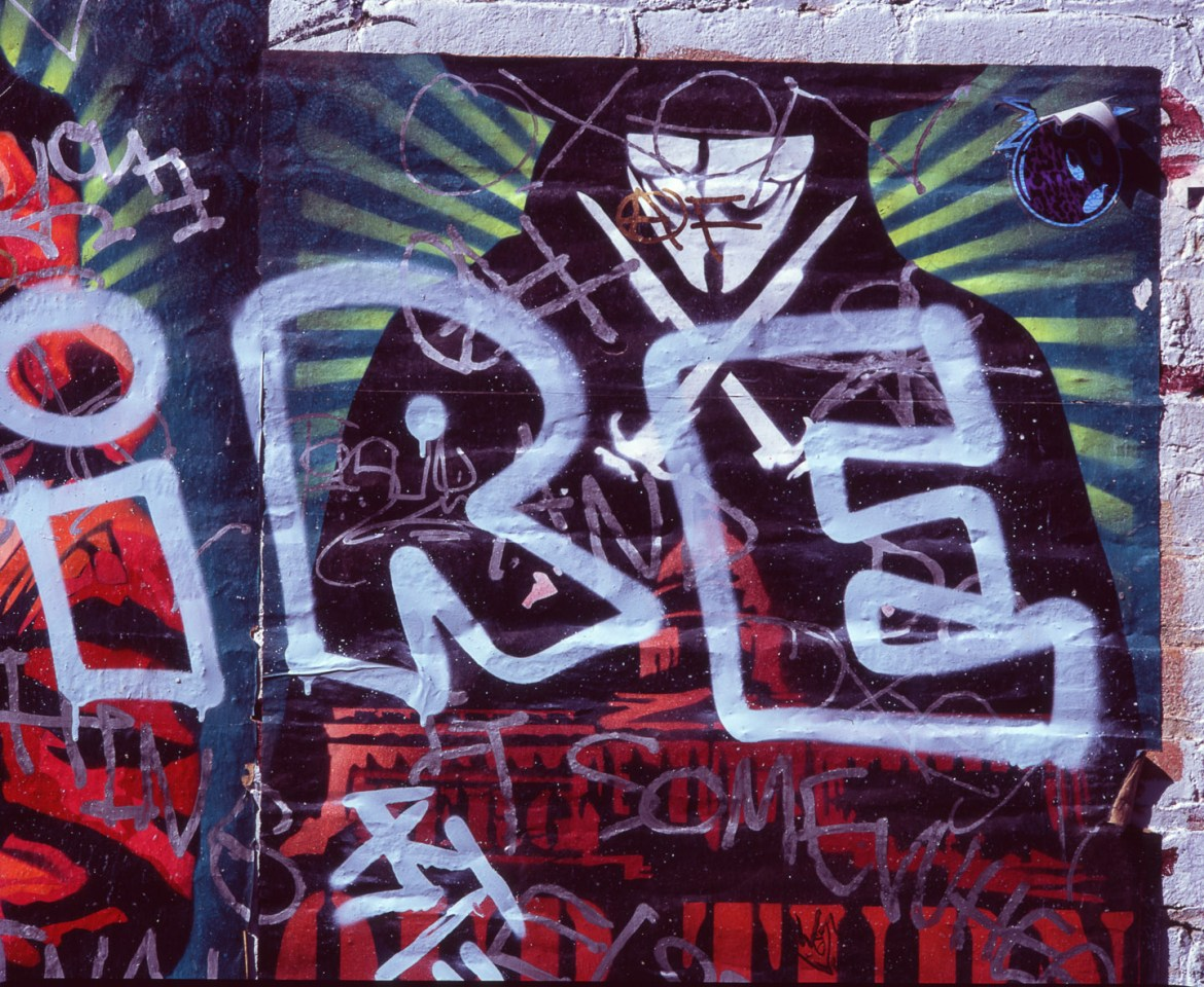 Graffiti and posters decorate an alley