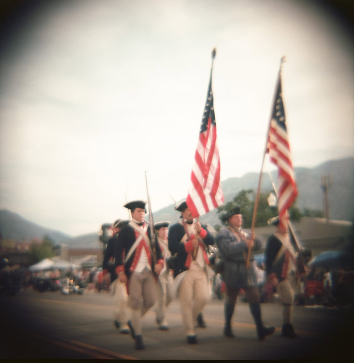 People dressed as Revolutionary War soldiers carry the American Flag