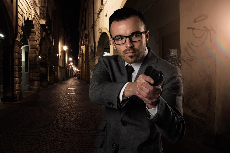 A spy walks the dark Italian streets with a gun