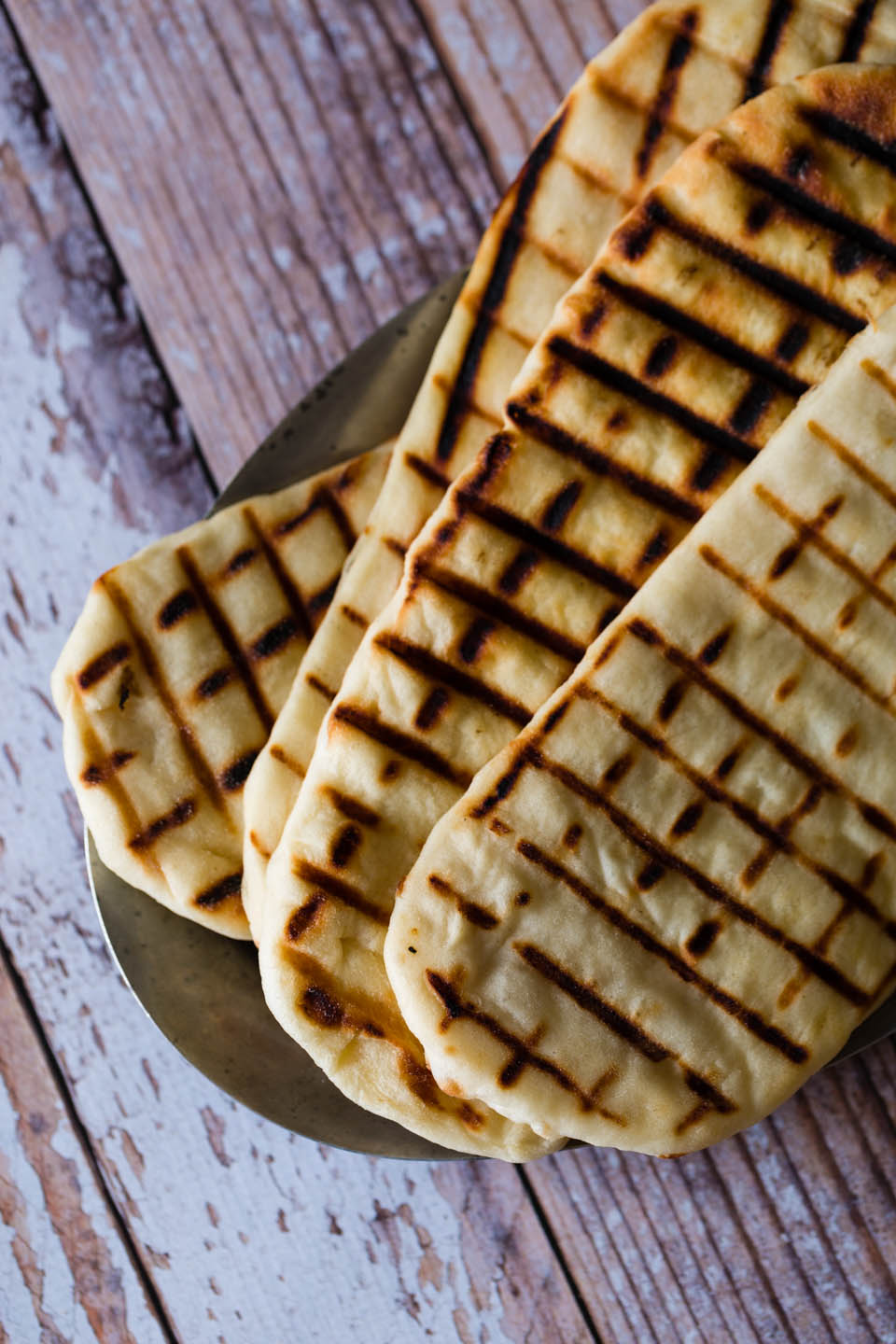 Naan bread on a rustic metal plate on a fake table top