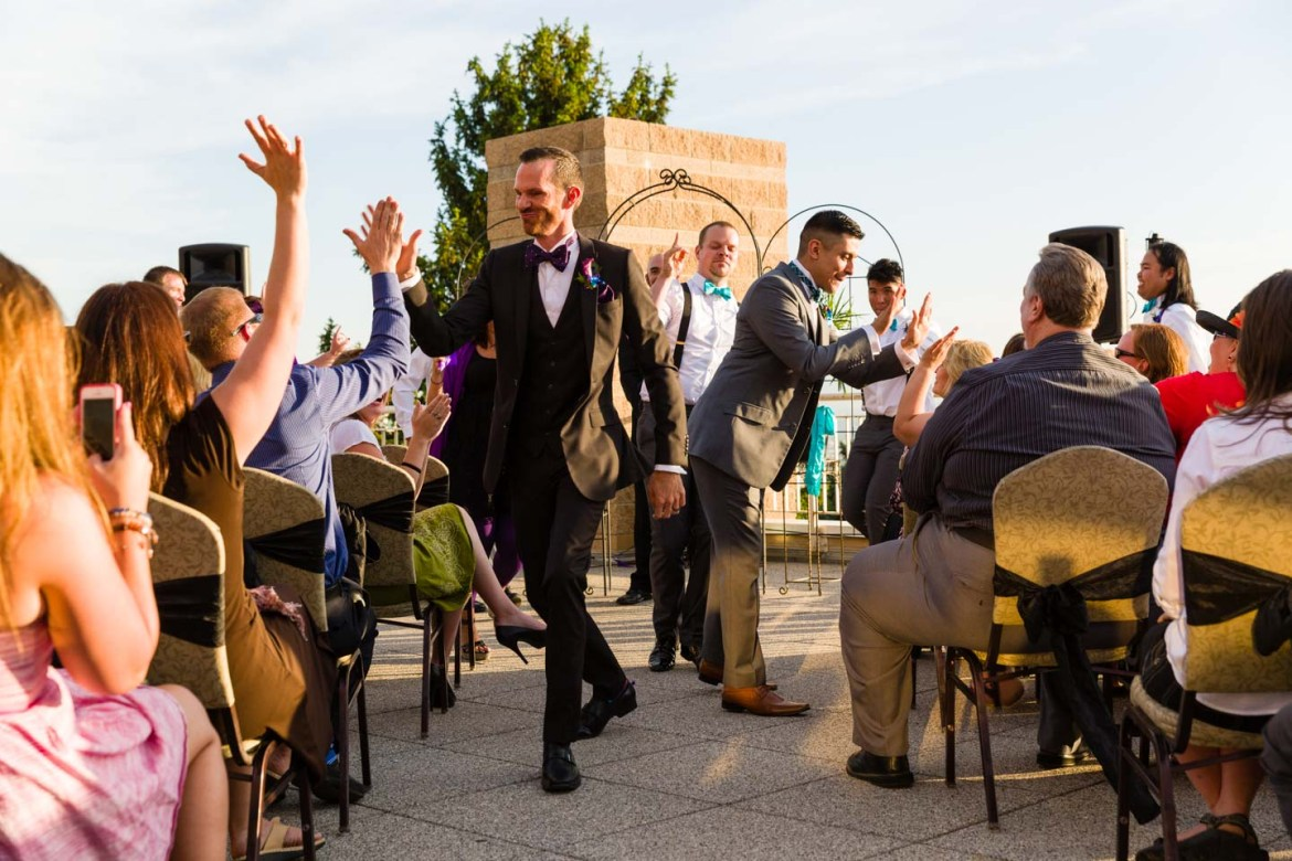 Grooms party down the aisle after wedding