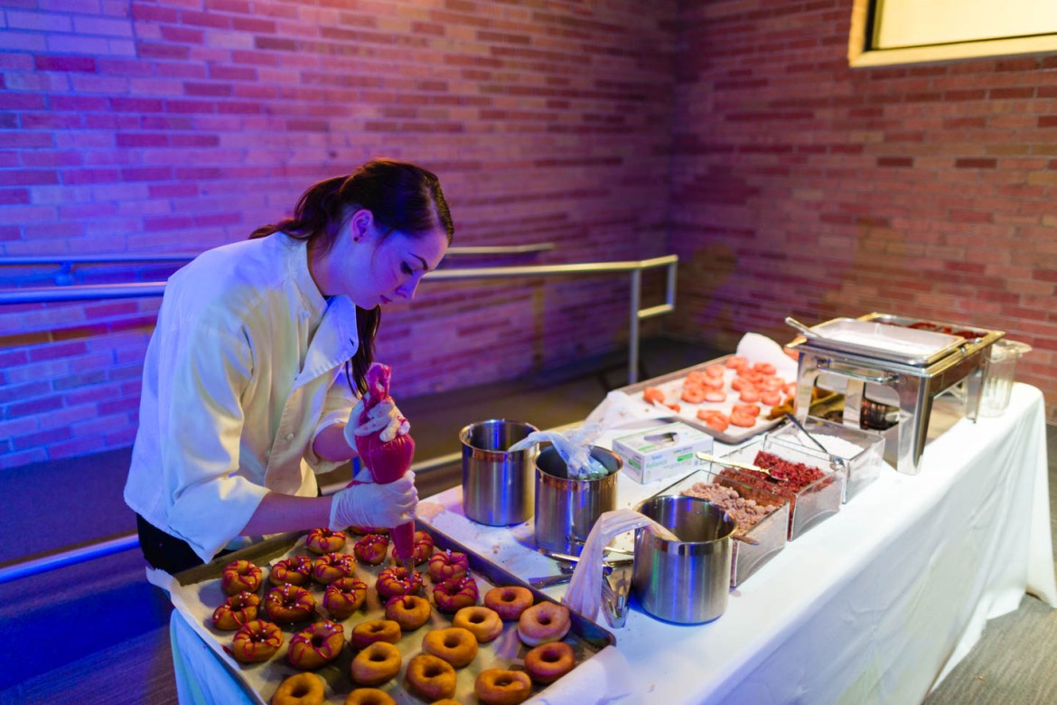A chef decorates the donuts