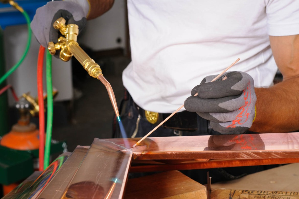 Erno welds while creating a copper finial