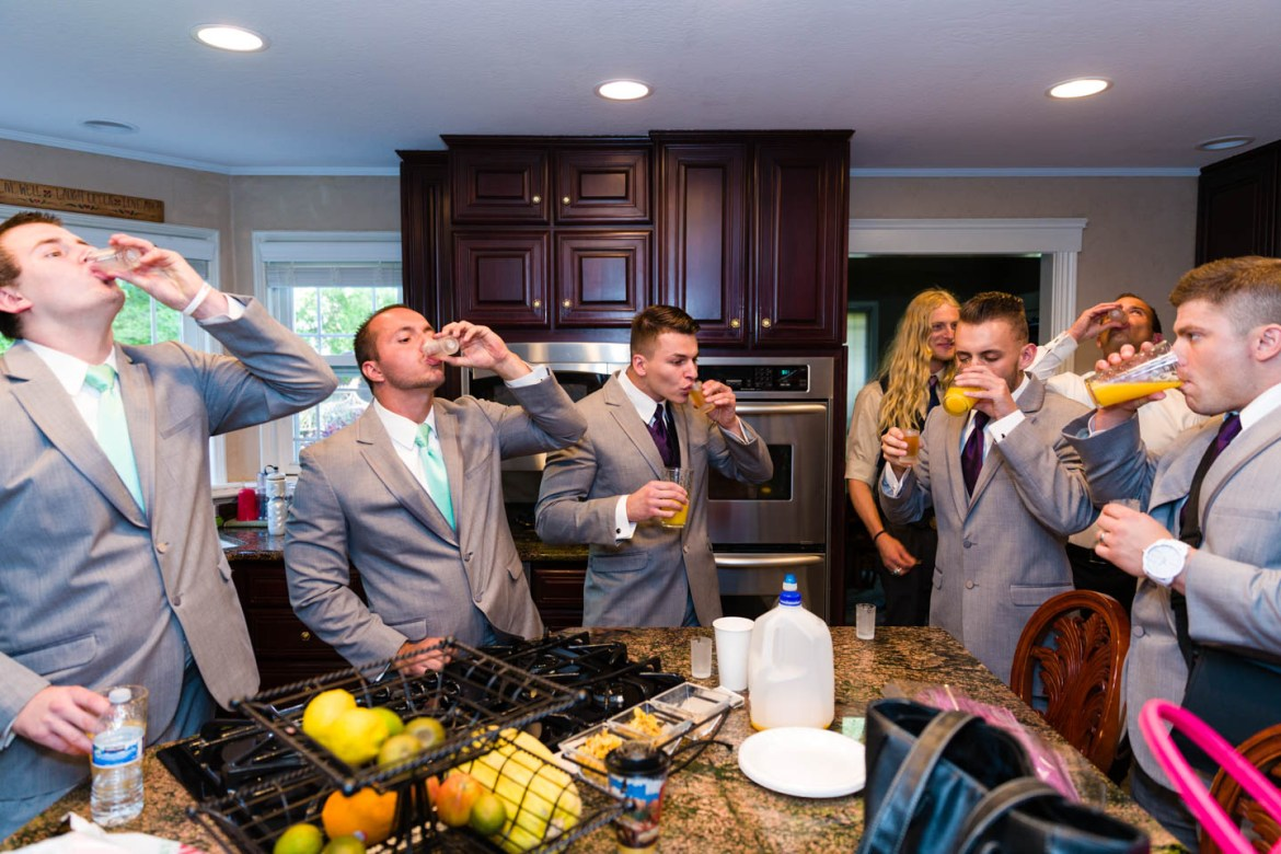 Groom and the groomsmen do shots before the wedding ceremony