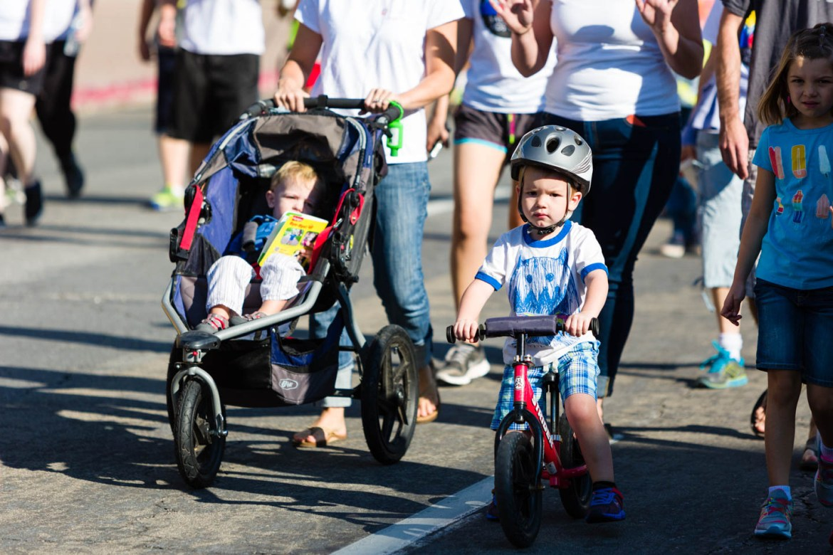 Family and kids ride bikes and walk for life