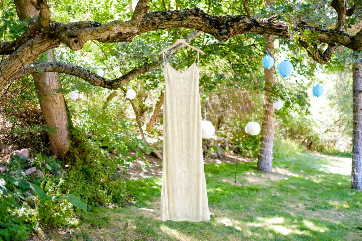 Bride's wedding dress hangs from the trees