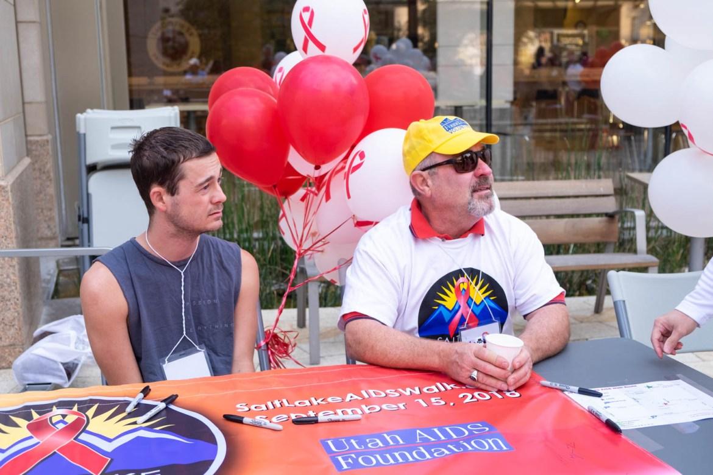Volunteers help people sign the banner