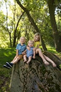 3 kids sitting on a large rock