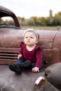 Baby girl with a grumpy face on an antique truck