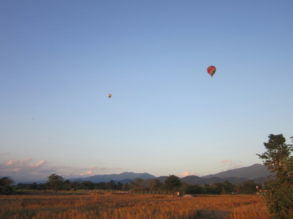 2 hot air ballons flying above fields in Vang Vieng in Laos
