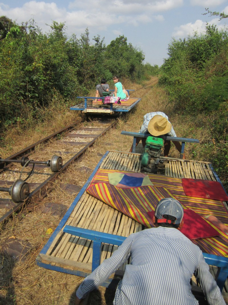 The bamboo train in Battambang, Cambodia. Drivers moving one train off the tracks so another can pass.