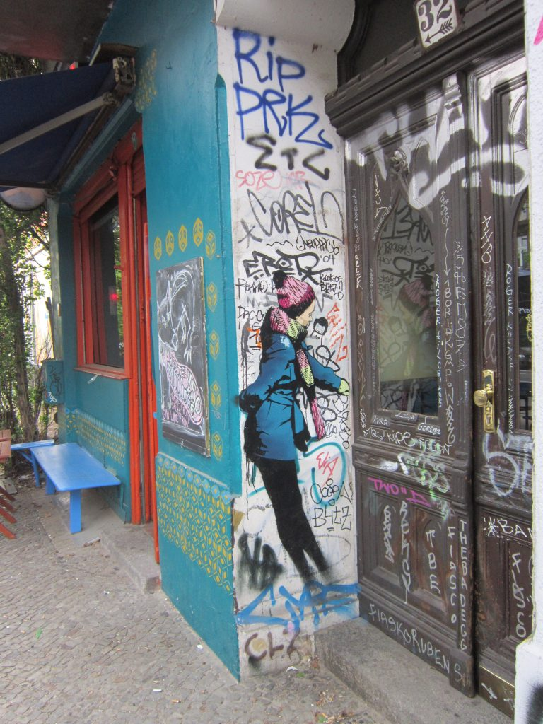 Things to do in berlin - street art. a girl painted in a doorway. surrounded by graffiti tags.