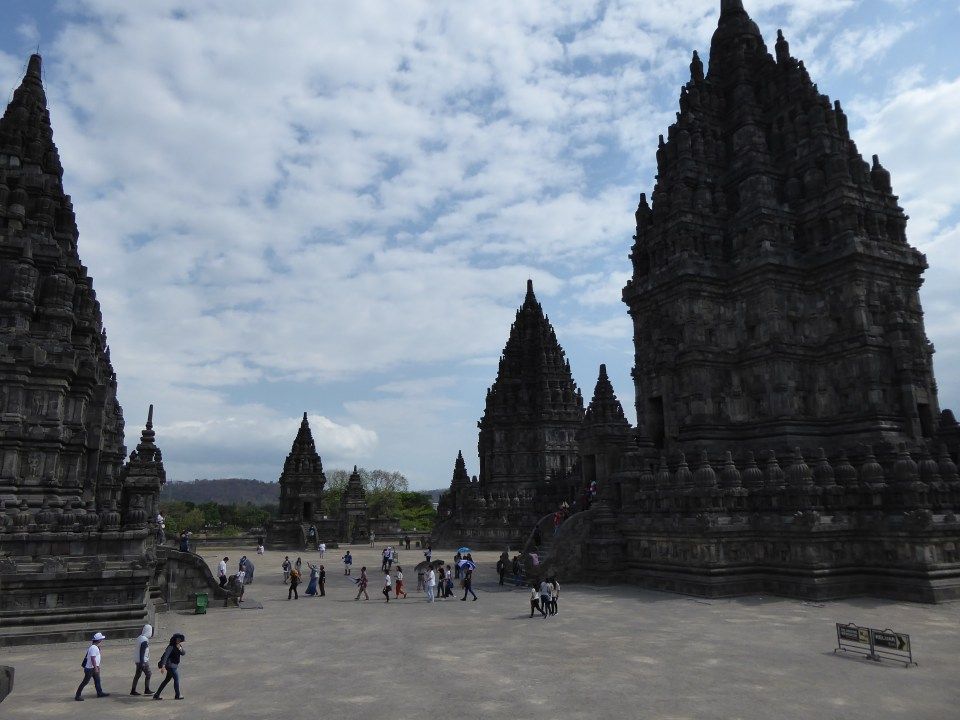 Yogyakarta Travel Guide - view form inside the Prambanan temple complex, featurign tmeples and people wandering amongst them