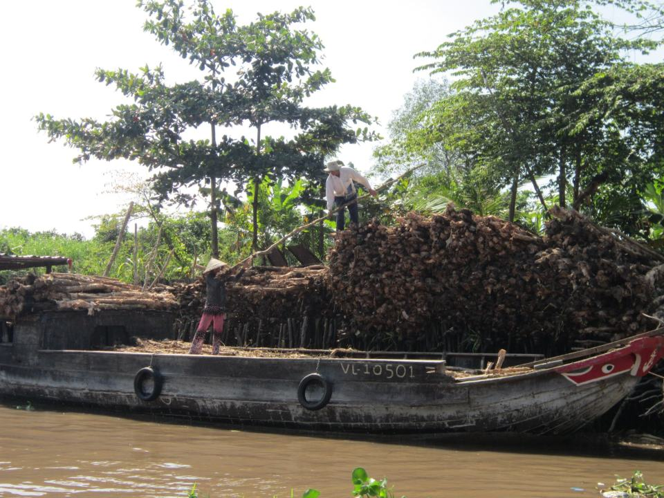 2 Locals working on a boat in the The Mekong Delta - Vietnam Backpacking Itinerary