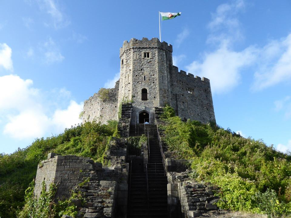 Looking up at the Norman Keep at Cardiff Castle. Welsh flag flying from the top. Blue skies.