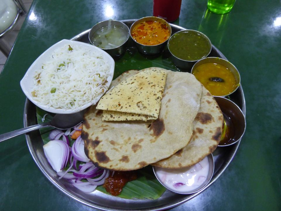 A Singapore Vegetarian Thali style meal. Including roce, bread and several curry and dip pots