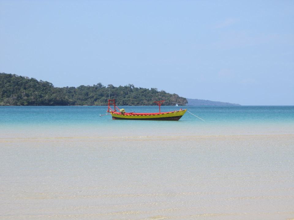 A yellow boat on calm blue water in M'pai bay, Koh Rong Sanloem, Cambodia.