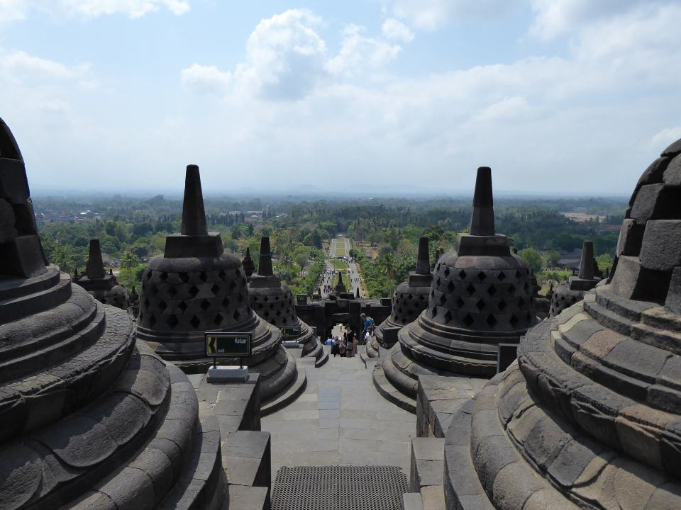 Looking out from the top of Borobudur, past Buddhist chedi's towards green tree's with a path running through the middle.