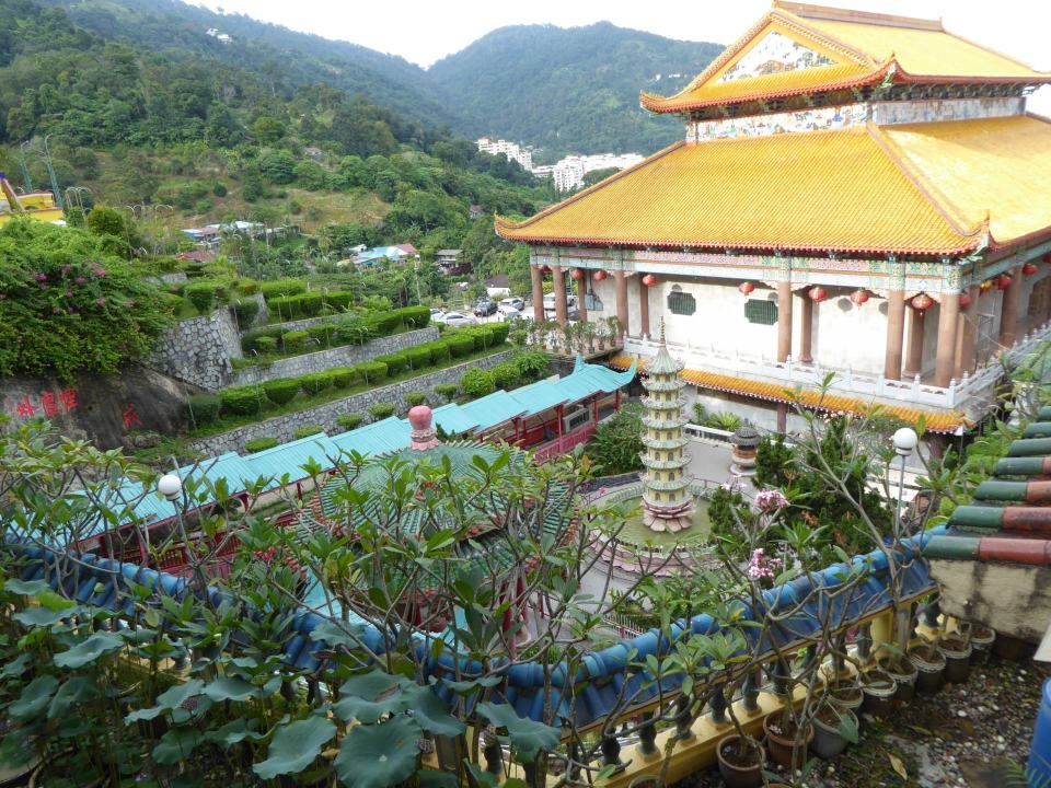 A view of part of Kek Lok Si temple, showign some of it's gardens with green hillsides in the background.