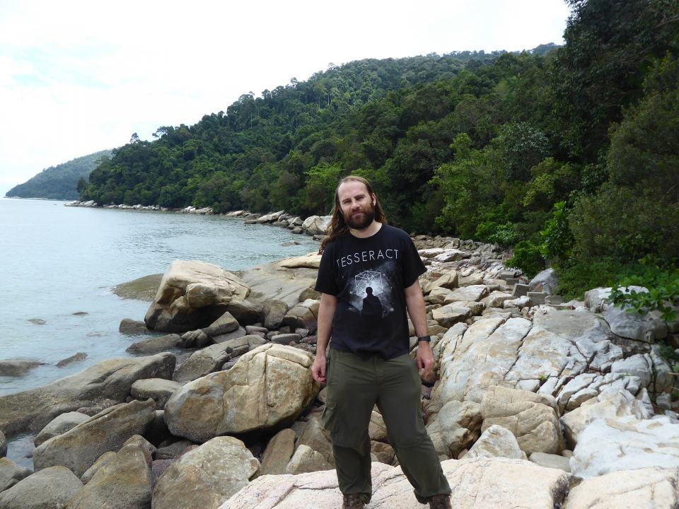 Dave Does The Travel Thing standing on the rocky coast of the island at Penang National Park, with the jungle behind. One of the shortest treks in Southeast Asia.