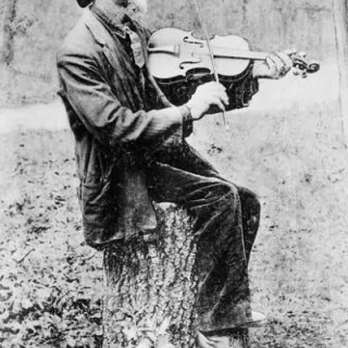 An Old Time Photo of a Man Playing a Fiddle