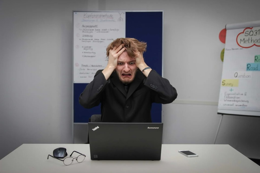 Photo of Frustrated Man Holds Head