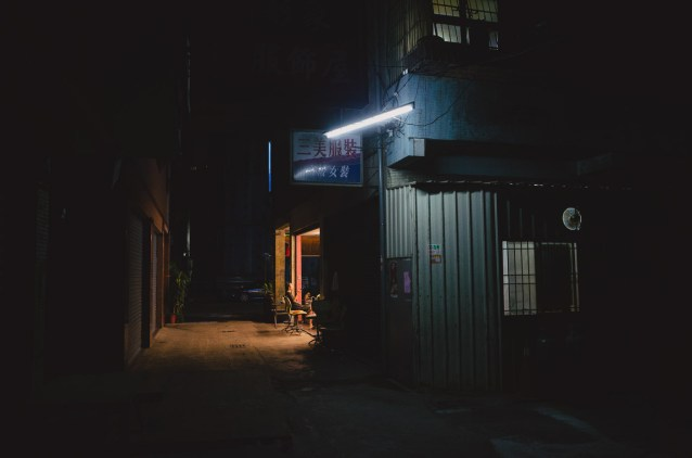 Light leaks out into an otherwise dark alley