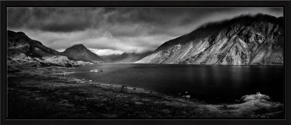 The golden winter's sun warming the mountains and screes around Wast Water in Wasdale on a stormy afternoon