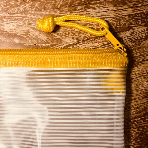 Items: stationery, paper etc. storage pouch (clear vinyl with yellow zipper)