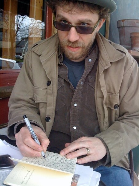 Carla Bergman snaps Dave (obv deep in thought) writing notes about Letters from Russia for article in Rainzine.